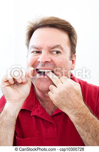 Man Flossing Teeth in the Mirror - csp10300728