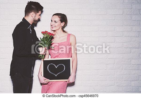 Man giving flowers to his girlfriend handsome young man giving man giving flowers to his girlfriend csp45646970 mightylinksfo