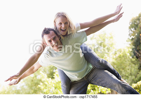 Man giving woman piggyback ride outdoors smiling - csp1717455
