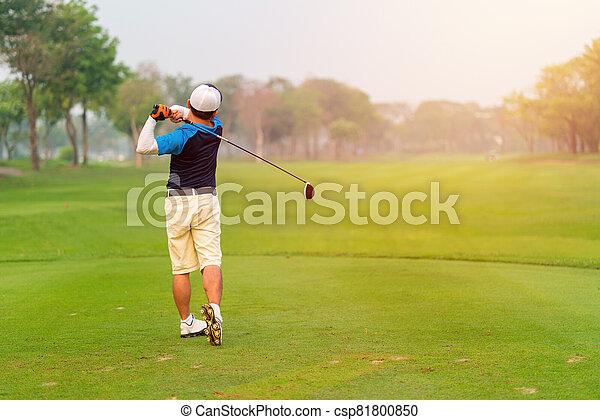 Man Golfer Hitting Ball with Club on Beatuiful Golf Course - csp81800850