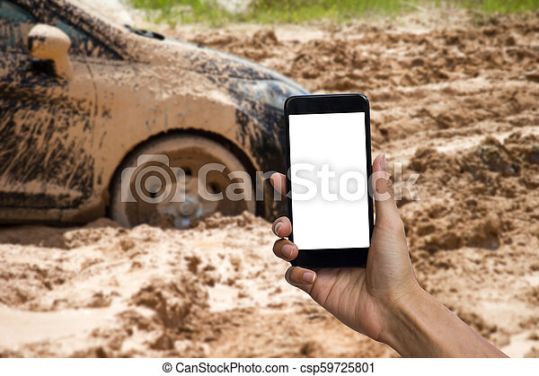 Man hand holding smartphone with white screen display use for mock up. Car tire stuck in the mud background. Car wheel in the mud clay can not run out. - csp59725801