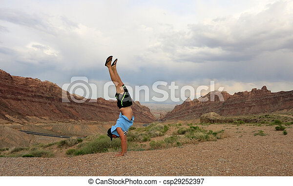 Man Handstands Spotted Wolf Canyon edge - csp29252397