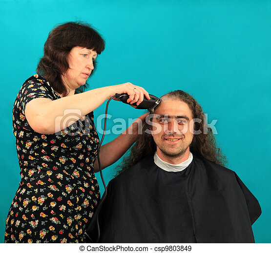 Man having an haircut on the green background - csp9803849