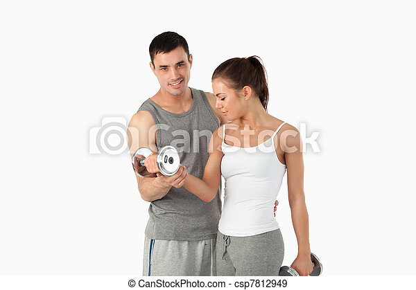 Man helping a cute woman to work out - csp7812949