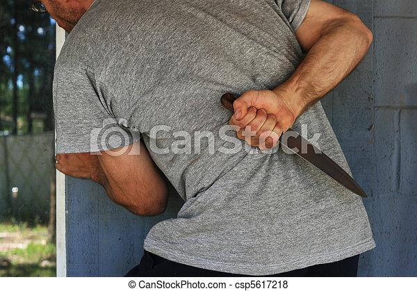 man hides knife - csp5617218