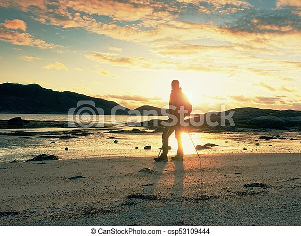 Man hiker backpacker walking with backpack on sea shore at sunny evening. Adventure, tourism active lifestyle. - csp53109444