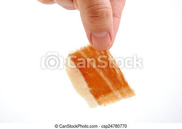 Man holding a serrano ham slice. Jabugo. Spanish tapa. - csp24780770