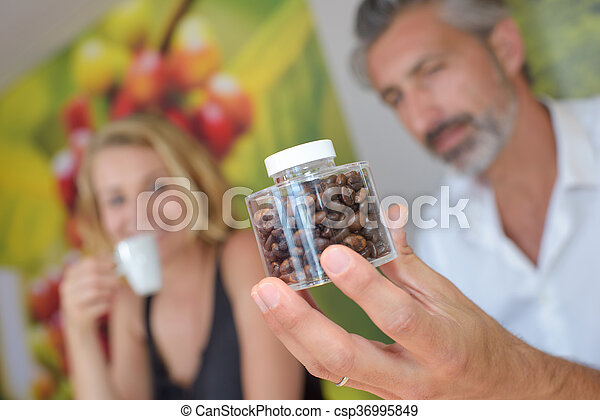 Man holding a transparent jar of coffee beans - csp36995849