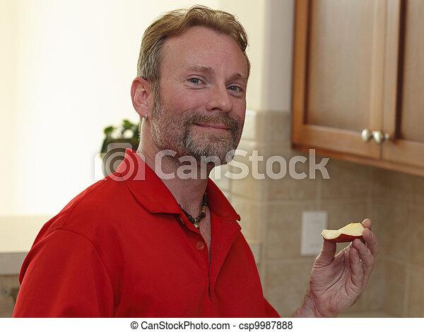 Man Holding an Apple Slice - csp9987888