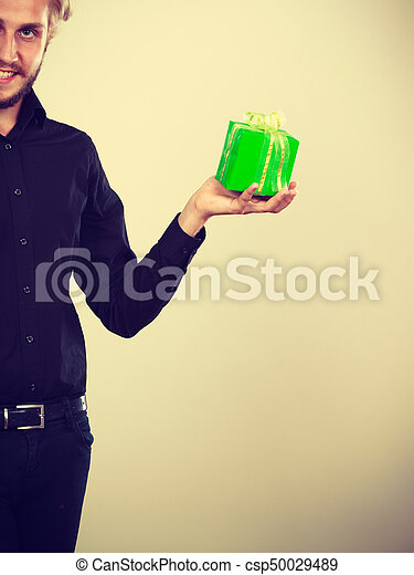 People celebrating xmas, love and happiness concept - cool young man holding small present green gift box in hand