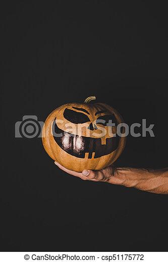man holding pumpkin with creepy face - csp51175772