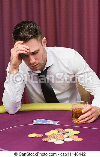 Man holding whiskey glass at poker table in casino.