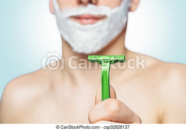 Man holds green razor - csp32828137
