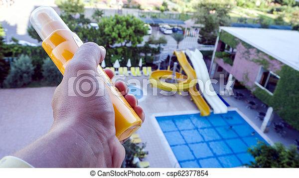 man holds sunscreen