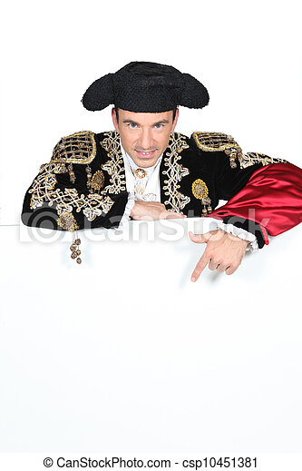 Man in a matador costume with a board blank for text or image - csp10451381