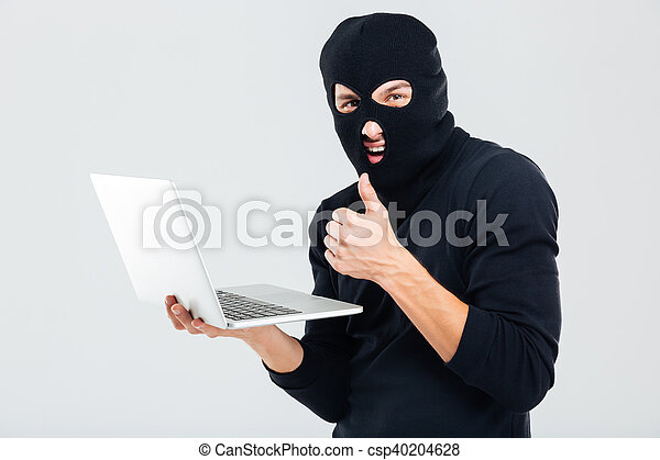 man-in-balaclava-using-laptop-and-stock-