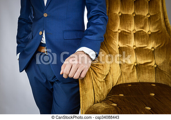 man in blue suit standing beside sofa - csp34088443