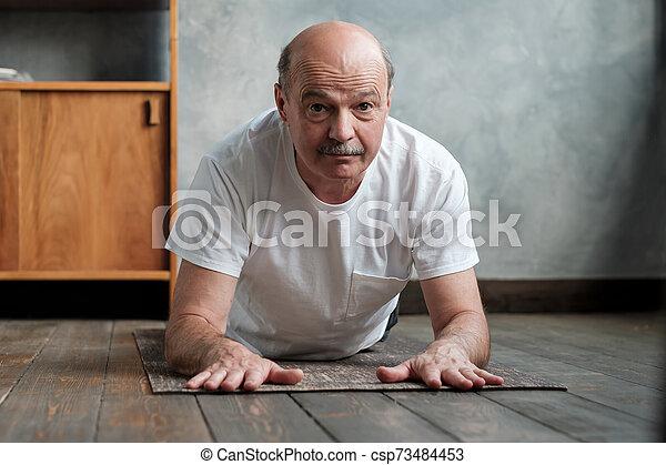 senior hispanic yoga man in cobra or sphinx pose