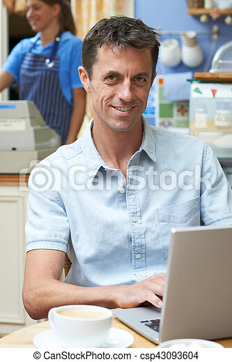 Man In Coffee Shop Using Laptop Computer - csp43093604