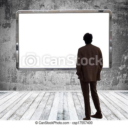 Man in gallery room looking at huge empty billboard - csp17557400