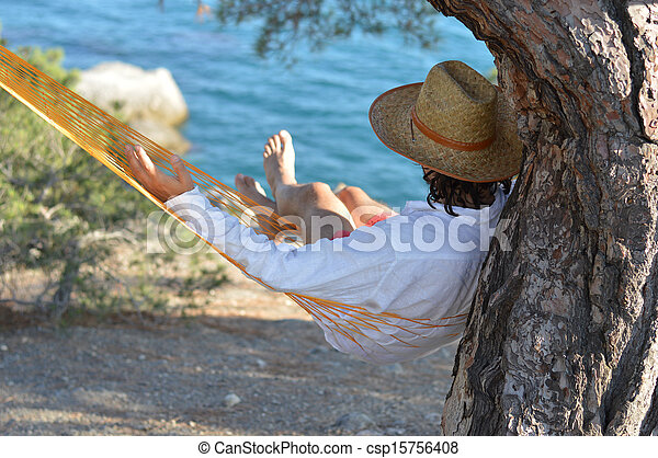 Man in hat in a hammock on pine tree in Crimea a summer day - csp15756408