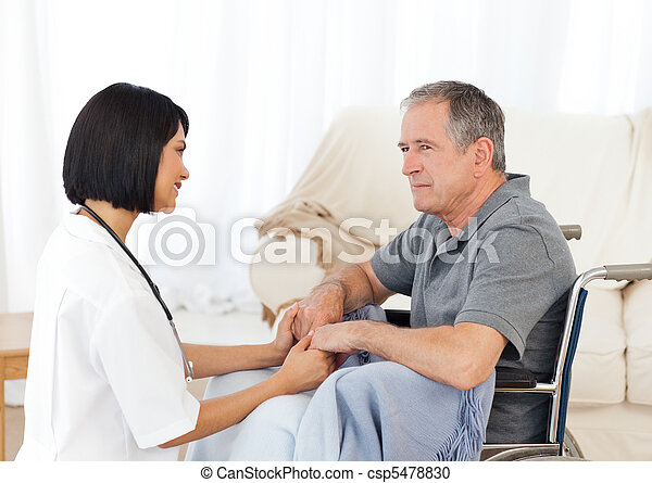 Man in his wheelchair with his nurse at home - csp5478830