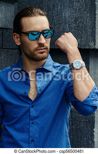 06b6b39e Man in jeans shirt. Handsome young man in jeans clothes stands on a ...