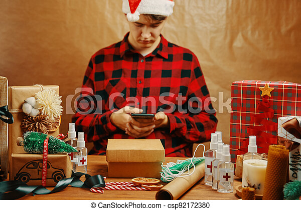 Man in plaid shirt with mobile phone in holiday decorations. - csp92172380