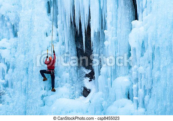 man in red coat climbing ice - csp8455023
