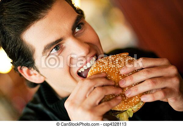 Man in restaurant eating hamburger - csp4328113