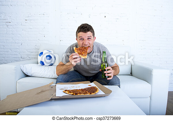 man in stress watching football game on television eating pizza drinking beer looking excited and anxious - csp37273669