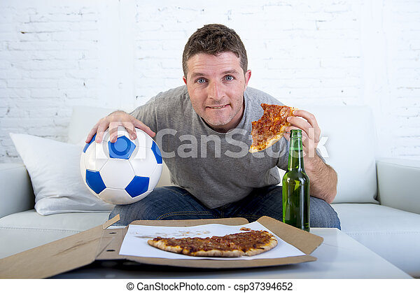 man in stress watching football game on television eating pizza drinking beer looking excited and anxious - csp37394652