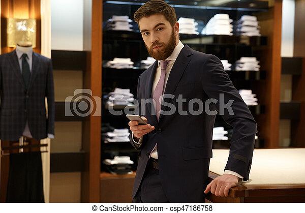 Man in suit holding smartphone - csp47186758
