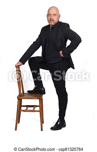 man in suit playing with a chair on white background - csp81320764