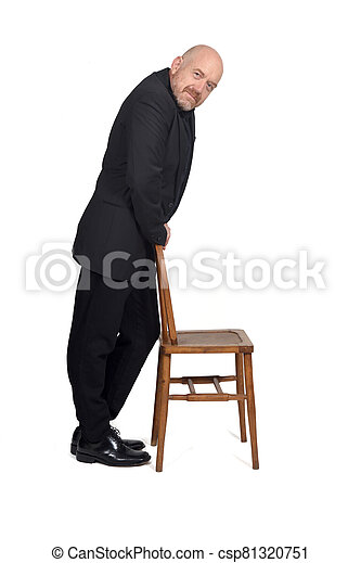 man in suit playing with a chair on white background - csp81320751