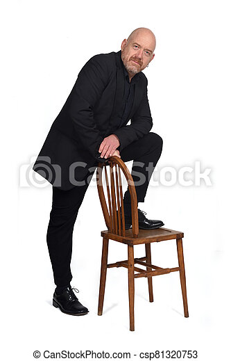 man in suit playing with a chair on white background - csp81320753