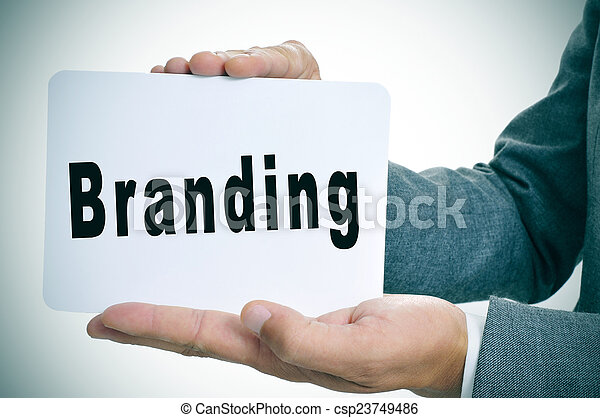 man in suit with a signboard with the word branding - csp23749486