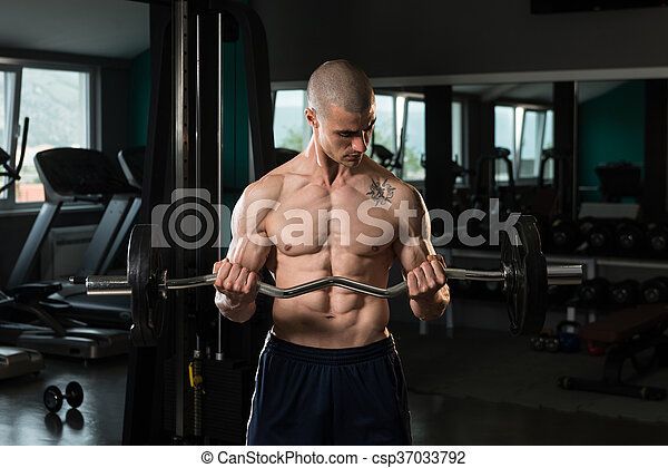 Man In The Gym Exercising Biceps With Barbell - csp37033792