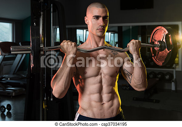 Man In The Gym Exercising Biceps With Barbell - csp37034195