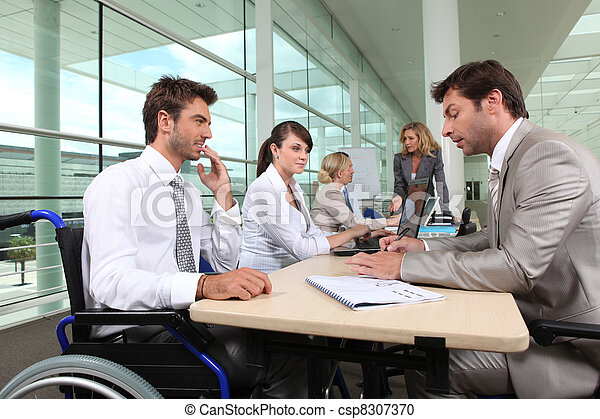 Man in wheelchair working in an office - csp8307370