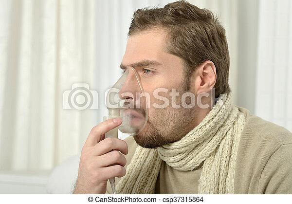 Man Inhaling Through Inhaler Mask - csp37315864