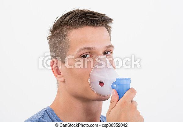 Man Inhaling Through Inhaler Mask - csp30352042