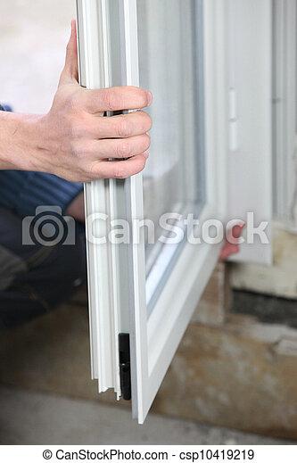 Man installing double glazed windows - csp10419219