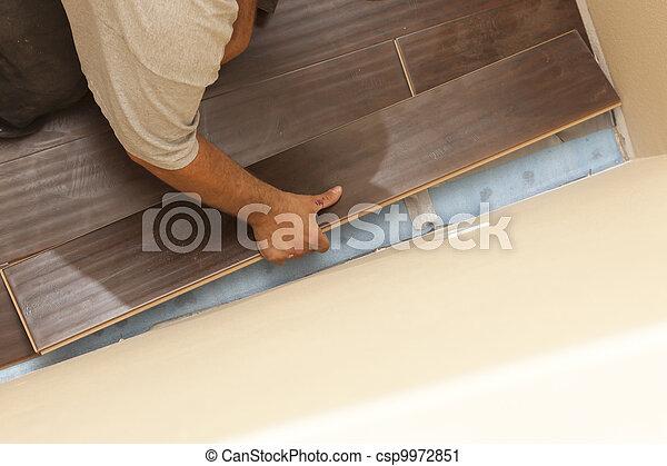 Man Installing New Laminate Wood Flooring - csp9972851