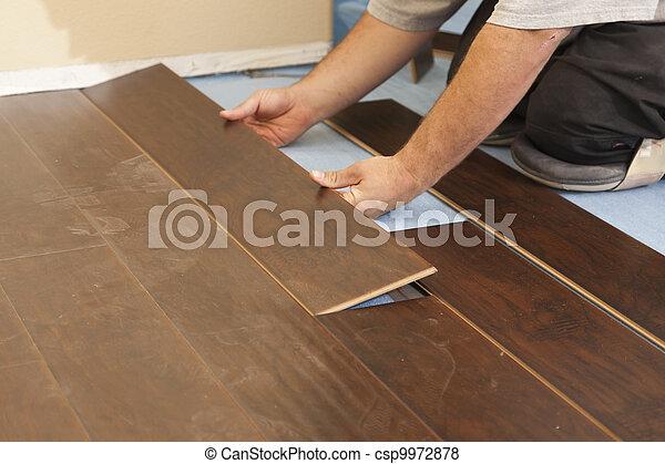Man Installing New Laminate Wood Flooring - csp9972878