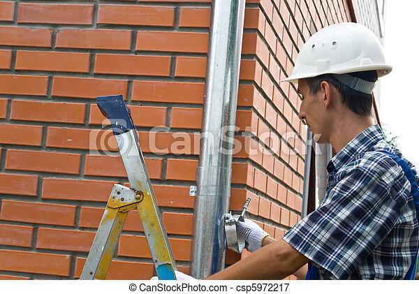 Man installing  rain gutter system - csp5972217