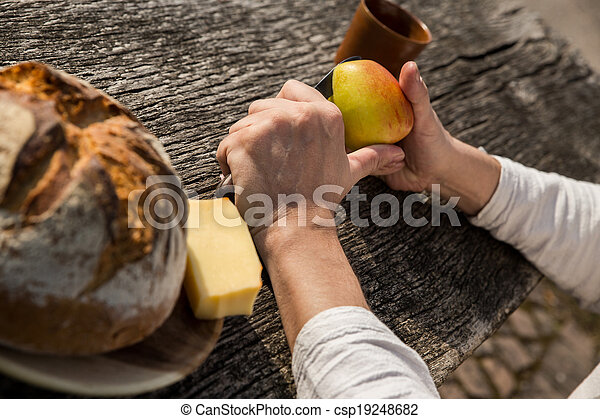man is cutting a apple in the nature - csp19248682