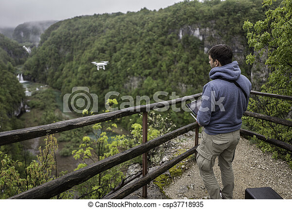 Man is operating the drone with a Plitvice waterfalls background - csp37718935
