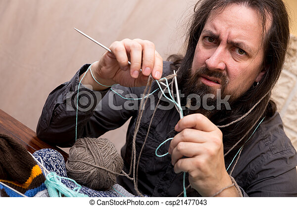 man is trying to knit - csp21477043