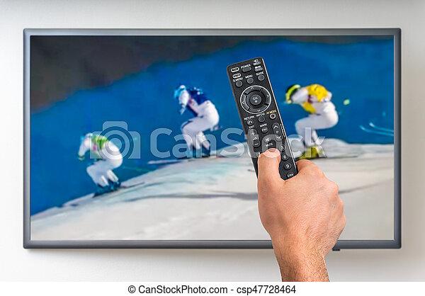 Man is watching winter skiing on TV - csp47728464